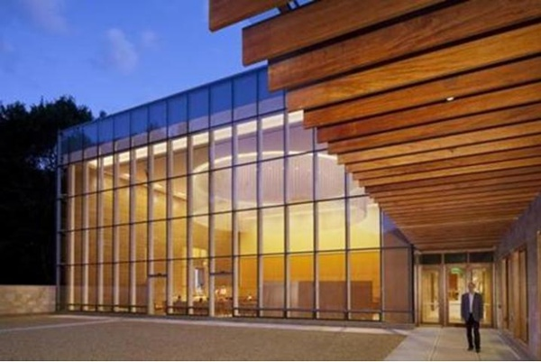 From the outside, the architecture of glass, warm-toned wood, and Jerusalem stone.